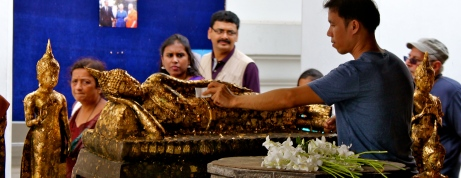 A man pays homage to God and King by laying pieces of gold leaf on this statue of Buddha.