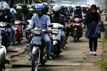 Motorcyclists encroach on the limited walking space on a South Jakarta roadside (photo: pulitzercenter.org)