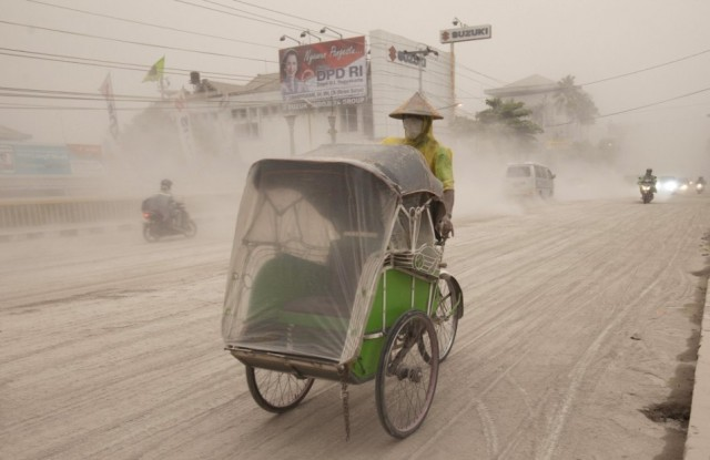 a man rides is becak through the falling ash (Reuters) (click for more photos from the Jakarta Globe)