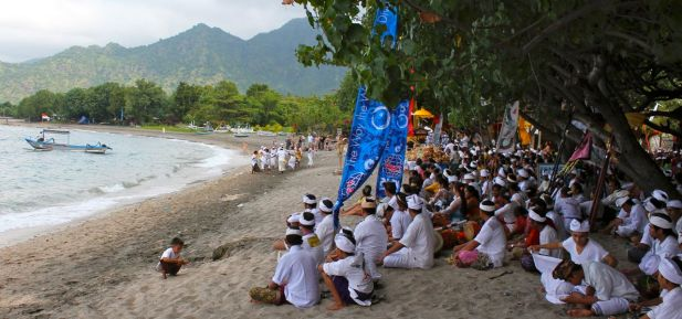 A Melasti ceremony takes place on the beach near tourist resorts in Pemuteran, Bali.