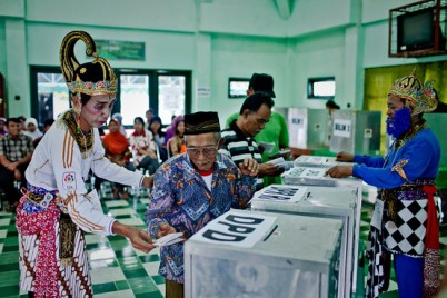 An election officer in traditional shadow puppet costume helps an elderly man vote at  in Yogyakarta (photo: the Wall Street Journal)