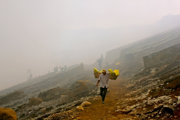 A porter emerges from the sulfurous mist on the path from Mount Ijen's crater.