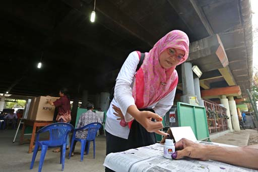 A woman dips her finger in ink after casting her vote during the legislative election at a polling station under the toll road in North Penjaringan, North Jakarta, on Wednesday ( Photo: Jakarta Post)