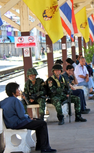 Soldiers at the Phitsanulok train station in Northern Thailand, under the flags of Thailand and the monarchy.