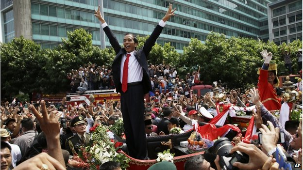 "Jokowi rode through massive crowds of supports in central Jakarta on Monday, flashing his trademark ""two finger salute"" (Photo: BBC)"