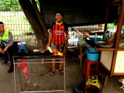 A boy fans the flames for the sate he sells under the staircase of a pedestrian overpass.