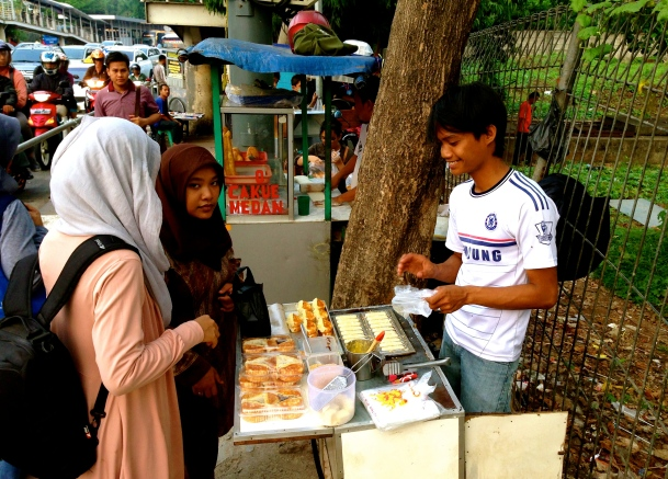 Two girls buy apem, a tasty snack, in the middle of a busy sidewalk in central Jakarta.